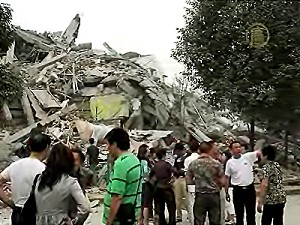 Residents look at a pile of rubble that was once a building until it was flattened by the Sichuan quake. (NTD News)