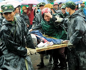 A mother screams in grief as Chinese soldiers carry away the body of her child, who was killed when a school collapsed during the 7.8 magnitude earthquake in Dujiangyan, in southwest China Sichuan province, May 13, 2008. (Teh Eng Koon/AFP/Getty Images)