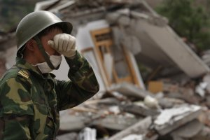 A Chinese soldier wipes his eyes while searching for earthquake victims in a quake ravaged town, May 15, 2008 in Beichuan, Sichuan province, China. Nearly 26,000 people remained buried in collapsed buildings, and the death toll is expected to climb. (Photo: Paula Bronstein/Getty Images)