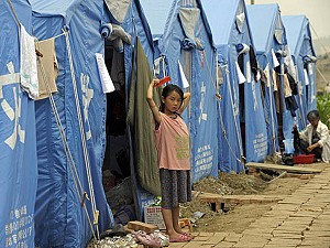 A young girl combs her hair while standing in front of tents providing temporary shelter in Anxian, in China's southwestern province of Sichuan. (Liu Jin/AFP/Getty Images)