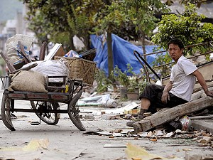 A man sits beside his damaged tricycle on a street in Leigu Town of Beichuan County in China's southwestern province of Sichuan on May 27, 2008. (Liu Jin/AFP/Getty Images)
