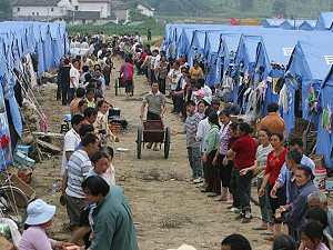 Earthquake survivors transport bricks to build a toilet a tent village in Anxian County of Sichuan Province, China. (China Photos/Getty Images)