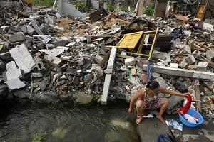 An earthquake survivor washes her clothes in a stream near her destroyed home. On June 8, a strong aftershock rocked a big lake formed by the earthquake which has been threatening to burst it banks and flood the surrounding area.  (Paula Bronstein/Getty Images)