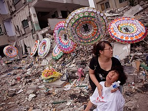 A woman whose child was killed when the Xinjian primary school collapsed in the May 12 earthquake, is comforted by a relative as she is overcome by grief during a commemoration of Children's Day on the rubble-strewn school campus on June 1, 2008 in Dujiangyan, Sichuan province, China. (Andrew Wong/Getty Images)