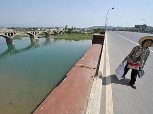 A woman walks on a bridge over the Qinglian river which connects to the Tangjiashan 'quake-lake' in the town of Qinglian, on the outskirts of the city of Mianyang, in China's southwestern province of Sichuan. (Teh Eng Koon/AFP/Getty Images)