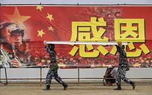 Two Chinese soldiers carry a board past a propaganda billboard in Mianzhu county, in China's southwestern province of Sichuan. (Liu Jin/AFP/Getty Images)