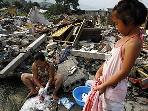 An earthquake survivor washes clothes in a stream while her daughter waits June 9, 2008 in Juilong, Sichuan province, China. (Paula Bronstein/Getty Images)