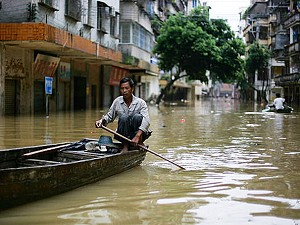A local resident paddles on flooded street in Zhaoqing of Guangdong Province, China. Since June 6, torrential rains in China's southern provinces have killed 176 people, and forced the evacuation of more than a million residents. (M.N. Chan/Getty Images)