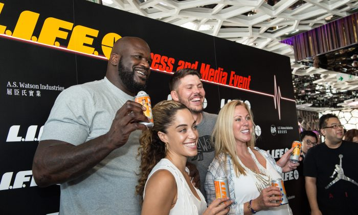 Mike Miller and wife Jenni stand together with Shaq O'Neal and his girlfriend Laticia at the Hong Kong launch ceremony of Miller's new L.I.F.E. drink, at Ozone, The Ritz Carlton, Hong Kong on August 18, 2015. (Bill Cox/Epoch Times)