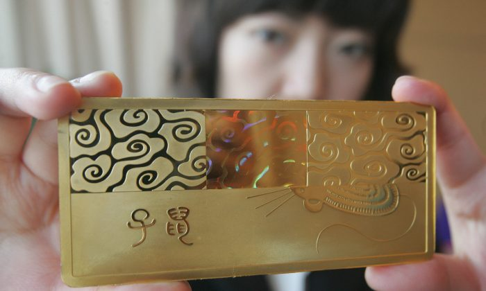 A Chinese staff shows off a gold bullion with a design of the rat in Beijing 17 December 2007. (STR/AFP/Getty Images)