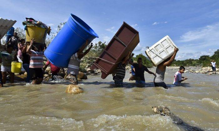 """Colombians deported from Venezuela return for their belongings and carry them across the Tachira River, border between the two countries, to Cucuta, in the Colombian North of Santander Department, on Aug. 25, 2015. Over a thousand Colombians """"who did not have any type of identification"""" had been deported since Friday, according to the governor of the Venezuelan state of Tachira, Jose Gregorio Vielma. On Aug. 21 Venezuela's President Nicolas Maduro indefinitely closed his country's border with Colombia and declared a state of emergency in part of the frontier region following an attack on Wednesday that wounded four people. (Luis Acosta/AFP/Getty Images)"""