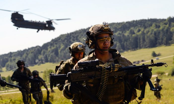 """American special forces soldiers advance as a Chinook helicopter takes off during the """"Swift Response"""" airborne training exercise in Hohenfels, southern Germany on Aug. 26, 2015. (Philipp Guelland/AFP/Getty Images)"""