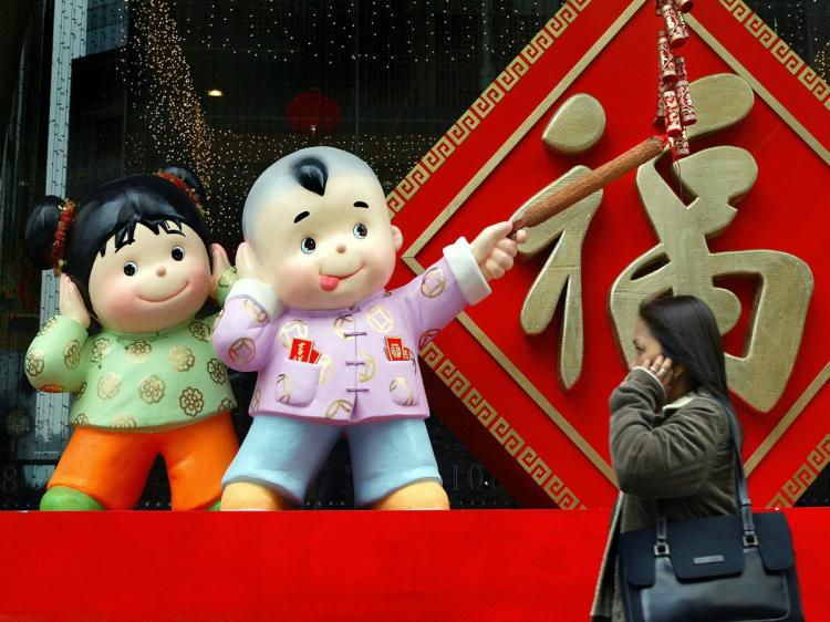LOUD FORTUNE: A woman walks by a Chinese New Year's decoration in Hong Kong. Children are depicted lighting firecrackers decorated with wishes for good fortune.  (Philippe Lopez/AFP/Getty Images)