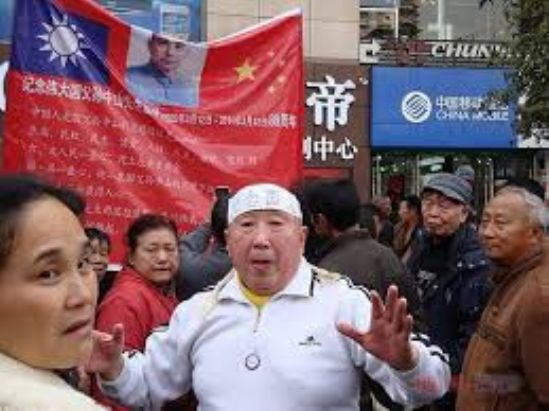 Han Liang speaks to a crowd in Chongqing, China. A poster behind him depicts the Nationalist and communist Chinese flags as well as republican Chinese leader Sun Yat-sen. (Boxun)
