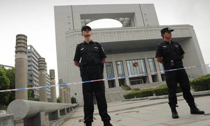 Policemen stand guard outside the Intermediate People's Court in Hefei, Anhui Province on Aug. 10, 2012. (Peter Parks/AFP/Getty Images)