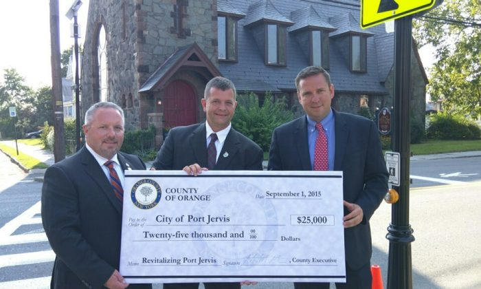 (L-R) Orange County Legislator Tom Faggione, Port Jervis Mayor Kelly Decker, and Orange County Executive Steven M. Neuhaus hold $25,000 check from the county to help revitalize Port Jervis. (Courtesy of the office of the Orange County Executive)