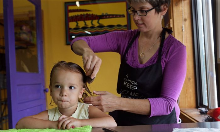 In a Friday, Aug. 28, 2015 photo, Charlotte Moore, 2, of Crestwood, receives a head lice screening from store owner and technician, Libby Lutz, at Lice Busters, a professional head lice removal company, in Richmond Heights, Mo.  A new strain of lice resistant to most treatment is causing worries as kids return to school, a time when outbreaks can occur and prove uncomfortable, and shame-inducing. (Cristina M. Fletes/St. Louis Post-Dispatch via AP)  EDWARDSVILLE INTELLIGENCER OUT; THE ALTON TELEGRAPH OUT; MANDATORY CREDIT