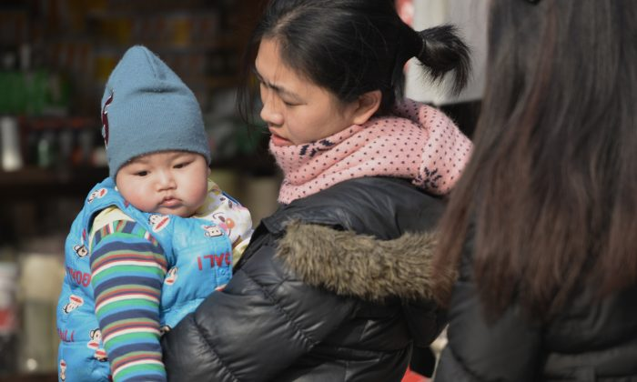 A mother carries her baby on a street in Shanghai in this file photo. (Peter Parks/AFP/Getty Images)
