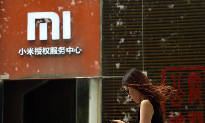 A woman walks past a Xiaomi logo outside a Xiaomi service center in Beijing on August 5, 2015. (Greg Baker/AFP/Getty Images)