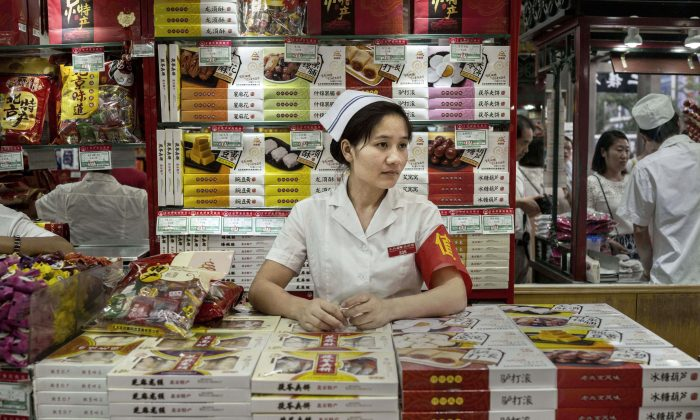 A Chinese retail clerk waits for customers at a shop on August 28, 2015 in Beijing, China. (Kevin Frayer/Getty Images)