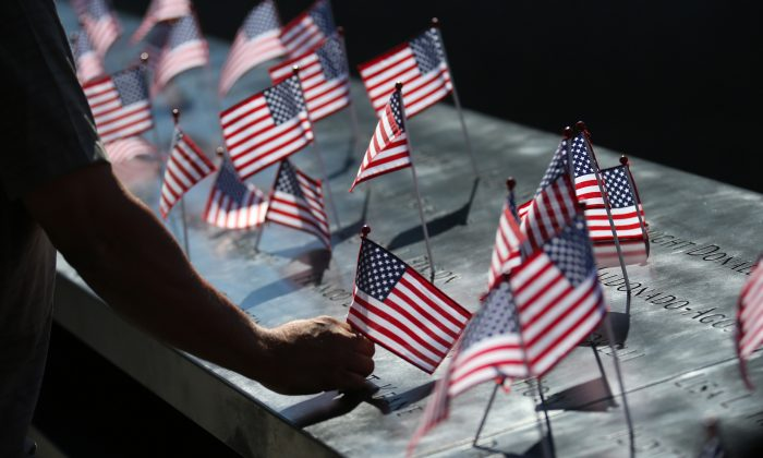 A man fixes an American flag that had fallen during memorial ceremonies for the eleventh anniversary of the terrorist attacks on lower Manhattan at the World Trade Center site in New York City, on Sept. 11, 2012. (Chang W. Lee/Getty Images)