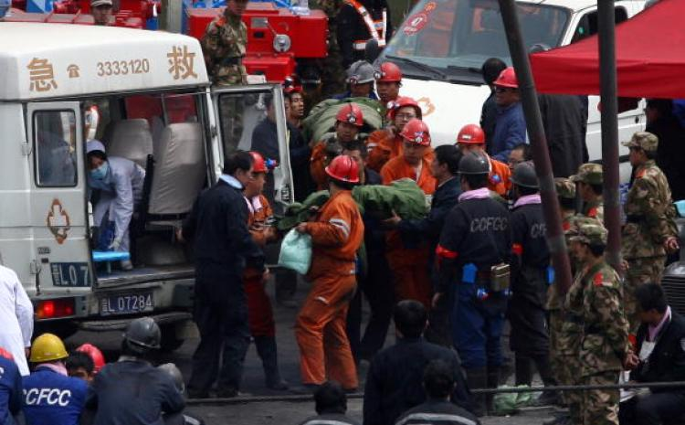 Workers wait outside the entrance to the Wangjialing coal mine as rescuers try to find more than 150 workers trapped in the flooded coal mine being built in northern China's Shanxi province on March 30, 2010. Workers accused their bosses of ignoring warning signs of danger as anger built over the accident after workers said water was noticed leaking into the pit days before the latest disaster to strike China's deadly mining industry. (PETER PARKS/AFP/Getty Images)