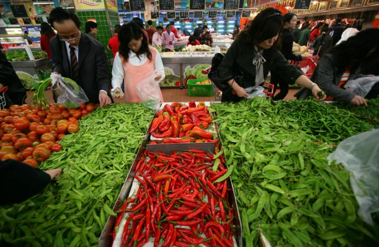 A resident of Chongqing buys vegetables at a supermarket.  (China Photos/Getty Images)