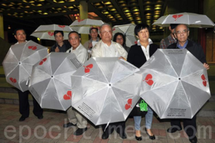 Nine members of the Hong Kong (China) Investment Rights Concern Group each carrying an umbrella with symbol and info of the group. (Kwong Tianming/Epoch Times)