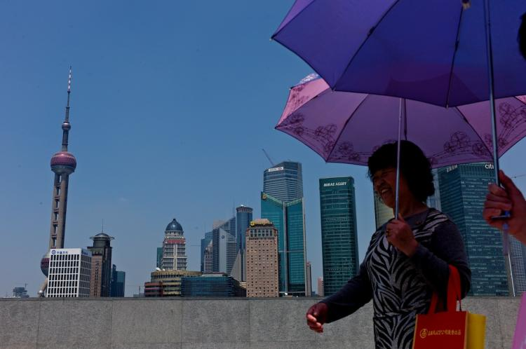 BUSINESS CENTER: Two women walk past the skyline of Shanghai's central business district. China is keen on developing its own global investment bank to rival competitors in Europe and the United States.