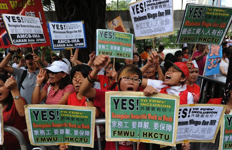 A group of domestic helpers protest for a minimum wage outside the Legislative Council in Hong Kong on July 14. (Mike Clarke/Getty Images)