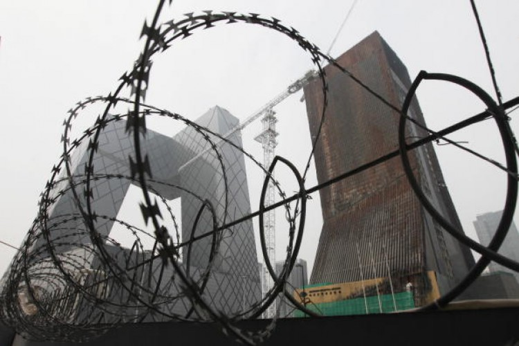 The China Central Television (CCTV) complex is pictured behind a barbed-wire fence in Beijing on Aug. 13, 2010.  (Lee/AFP/Getty Images)