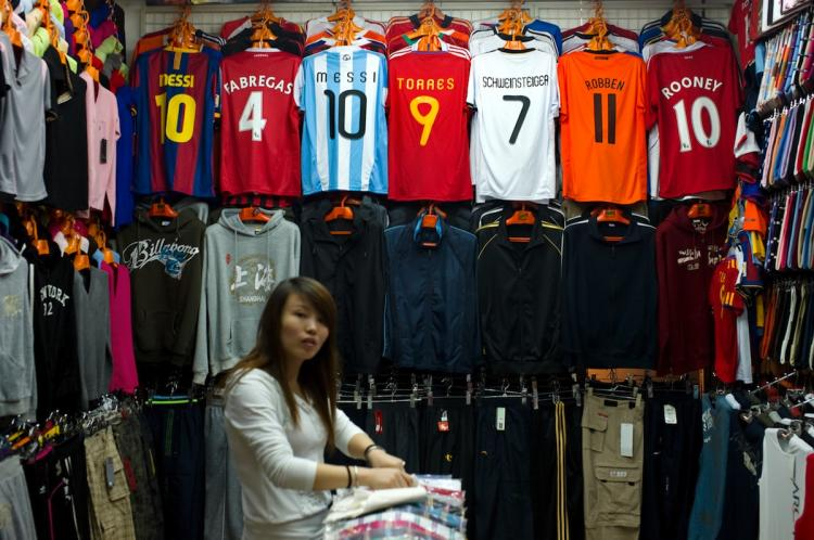 A Chinese shopkeeper arranges clothes next to fake FIFA football jerseys at a stall in a market that sells a lot of counterfeit merchandise in Shanghai on Sept. 3. Many experts are now questioning the United States's actions--or lack thereof--in combating patent infringements. (Philippe Lopez/Getty Images)