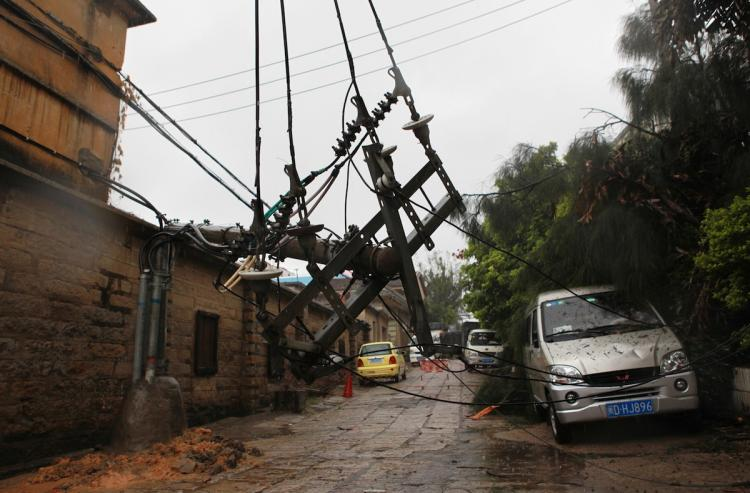 A fallen electric pole lies across a street in Xiamen, southeast China's Fujian province, on September 20. China warned of flash floods and landslides as Typhoon Fanapi made landfall on the mainland, one day after slamming Taiwan with heavy rains, which left more than 100 injured on the island. (STR/Getty Images)