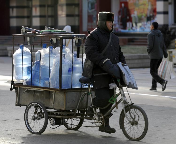 A worker cycles with mineral water for delivery in a street in downtown Beijing on December 29, 2010. The quality of China's tap water was raised on World Water Day. Reports and statements by professionals all point to a drinking water crisis.  (Liu Jin/Getty Images )
