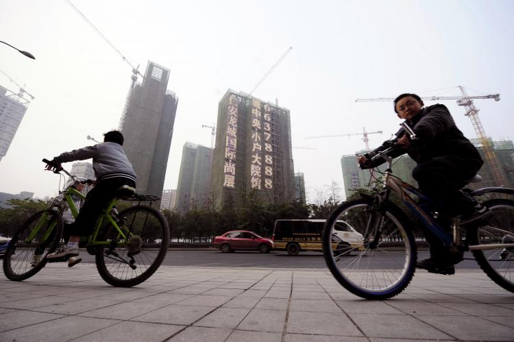 Cyclists ride past a construction site in southwest China's Chongqing municipality on Jan. 28. China launched a long-awaited property tax in two of the country's biggest cities, but the mayor of Chongqing in the southwest warned the measure was not a cure-all for soaring prices. (STR/AFP/Getty Images)