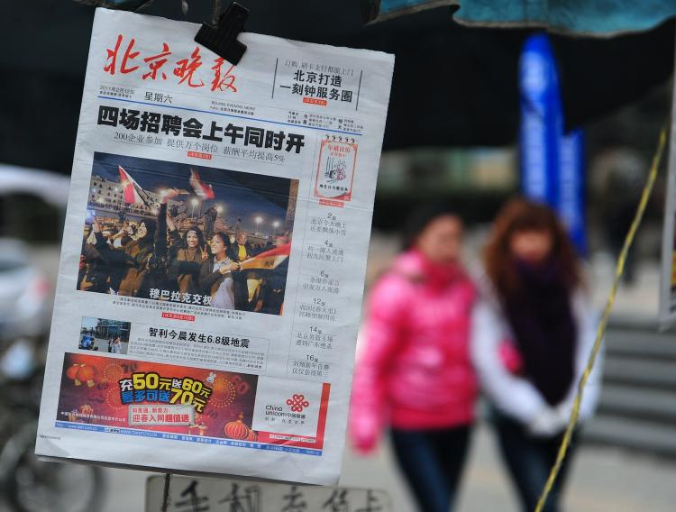 A copy of the Beijing Evening News with front page coverage about Egypt hangs on display at a news stand on February 12. China's tightly-controlled media reported news of Hosni Mubarak yielding to massive protests, but glossed over details of the popular uprising and emphasized the need to restore order. A sign that the unrest is worrying Beijing.   (Frederic J. Brown/Getty Images)