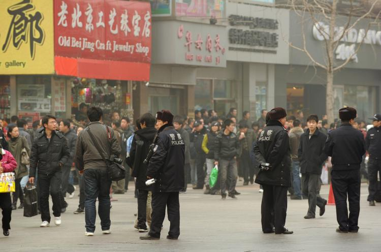 Police keep watch along the Wanfujing shopping street in Beijing after protesters gathered on February 20, 2011. A website claiming to represent China's homegrown Jasmine Revolution has called on the populace to take to the streets, every Saturday at 6:00pm.   (Peter Parks/Getty Images)