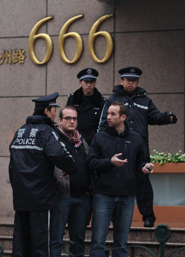 Foreign journalists are detained by Chinese policemen in a street leading to a designated demonstration site in Shanghai on March 6. Authorities in China have shown increasing nervousness about the Internet's power to mobilize ordinary citizens in the wake of unrest in the Arab world, and the subsequent online call for anti-government 'Jasmine' rallies at home. (Philippe Lopez/Getty Images )