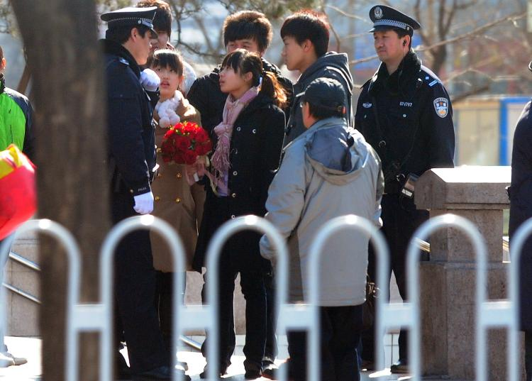 A woman carrying a bouquet of flowers is questioned by policemen on patrol near the Xidan shopping district in Beiijng on March 6, amid heightened security with the ruling Communist Party's annual parliament underway.  (AFP/Getty Images)