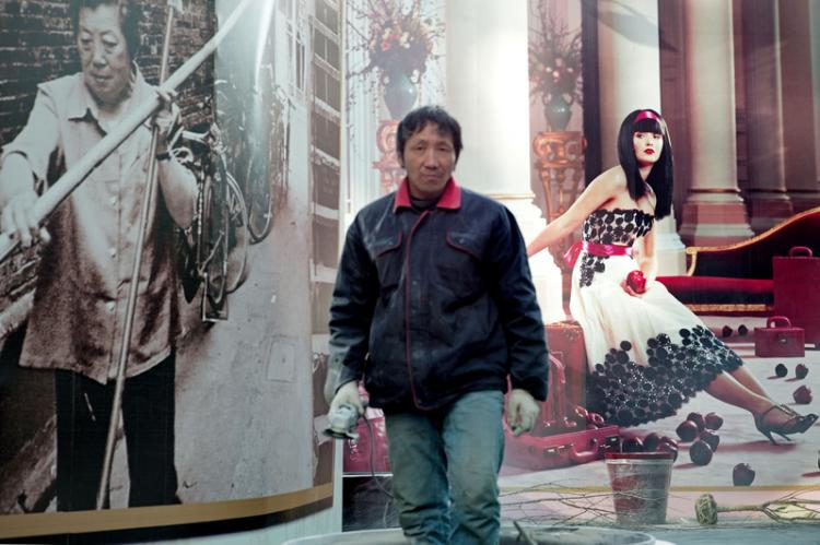 A worker stands in front of a poster of a luxury real estate project in Shanghai, China, Jan. 2011.  (Getty Images)