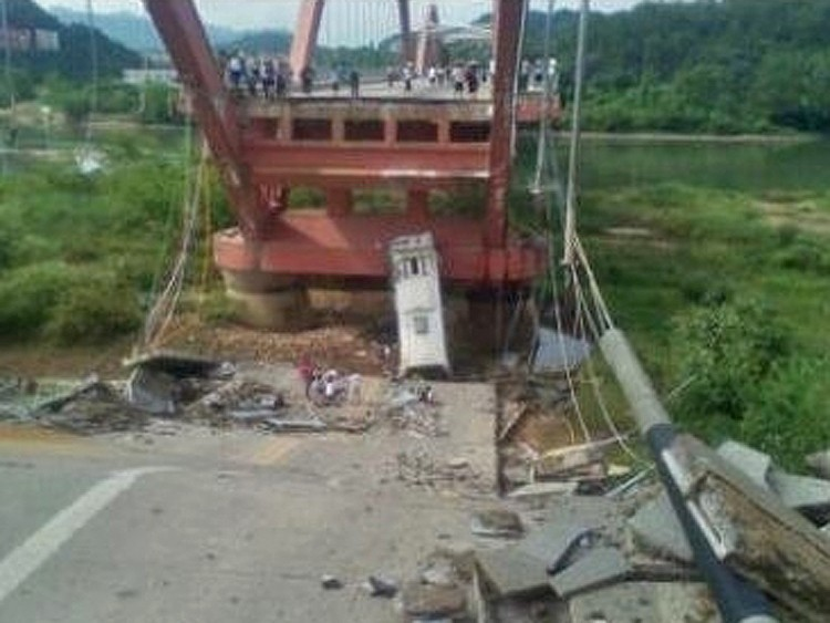 One third of the Wuyi mountain bridge in Fujian province collapsed on July 14, 2011, causing a full tourist bus to fall off the bridge. The bus driver died at the scene. (Weibo.com)