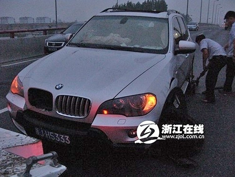 A BMW got stuck in a hole in the Third Qianjiang River Bridge in Hangzhou at 2 a.m. on July 15, 2011.  (Weibo.com)