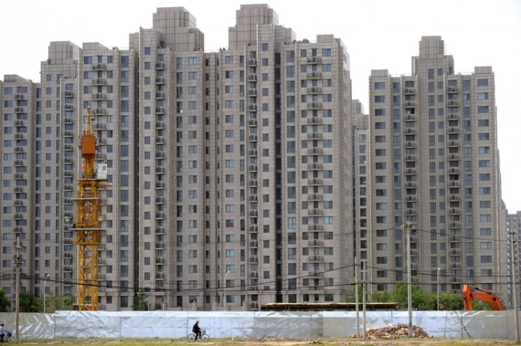 A man on a bicycle is riding past a real-estate development in Beijing. (Getty Images)
