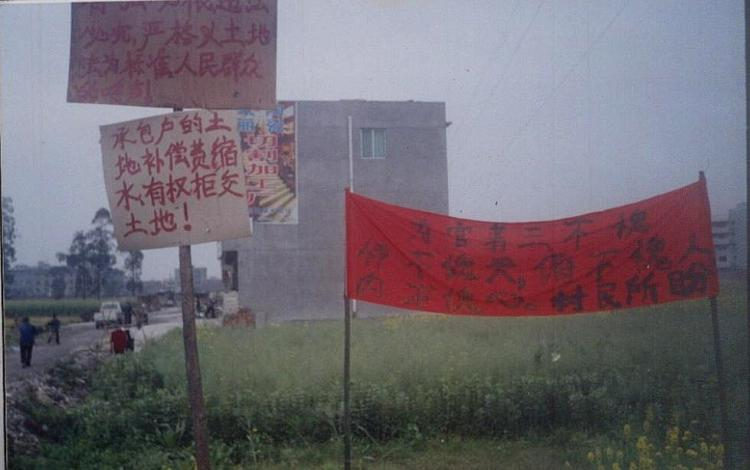 Evicted Chinese villagers hang banners to protest unfair land expropriation.   (The Epoch Times)