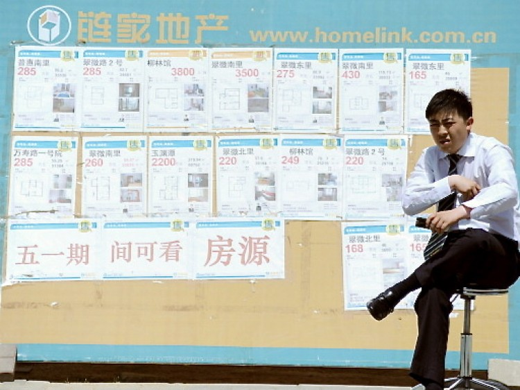 A property agent sitting in front of a board posting various property sales as he waits for house buyers by a street in Beijing. (Gou Yige/AFP/Getty Images)