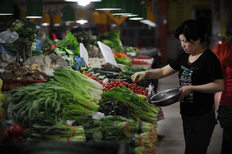 People shop for vegetables in a market in Beijing on May 11, 2011. The communist officials have their own safe food supply. (Peter Parks/AFP/Getty Images)