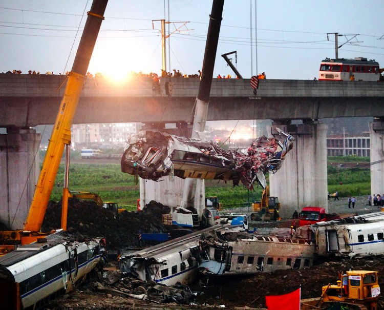 A mangled train car is hoisted away after the deadly Wenzhou collision of two trains on July 24, in China. (ChinaFotoPress/Getty Images)