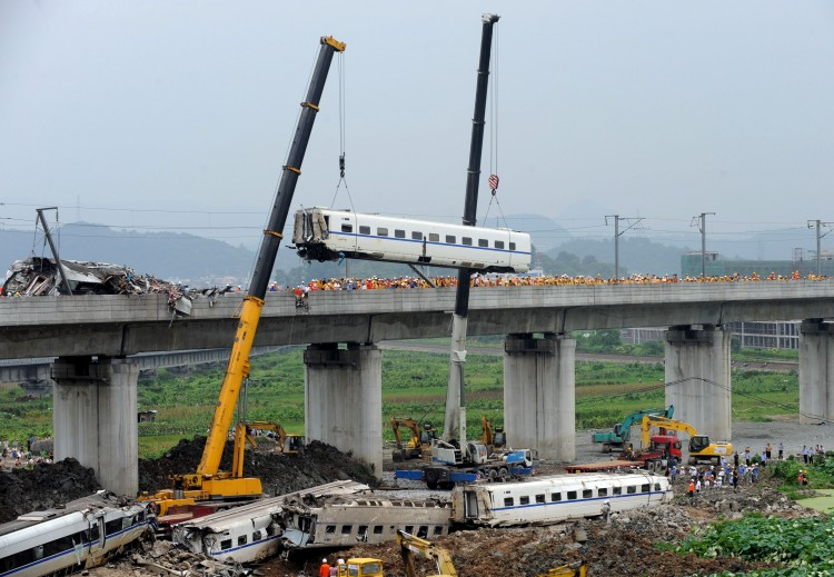 Following a fatal bullet train crash in eastern China, excavators arrive at the site to bury the fallen train cars. (STR/AFP/Getty Images)