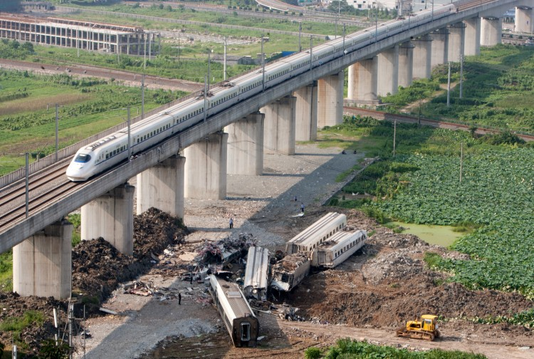 COLLIDING BULLETS: Despite the wreckage of two other high-speed trains which collided two days earlier, bullet trains have already begun running on a viaduct in the eastern Chinese province of Zhejiang on July 25. (STR/AFP/Getty Images)