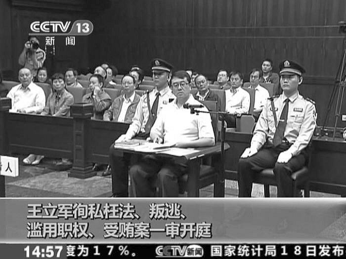 In a screen grab from a video released by Chinese Central TV, Wang Lijun is seen at his trial on Sept. 18, in Chengdu, China. The Chinese characters at the bottom of the image list the four charges against Wang. (Epoch Times)